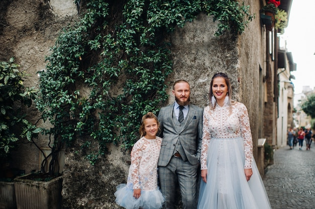 A happy young family walks through the old town of sirmione in italy.stylish family in italy on a walk.