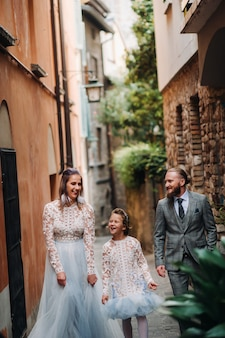 A happy young family walks through the old town of sirmione in italy
