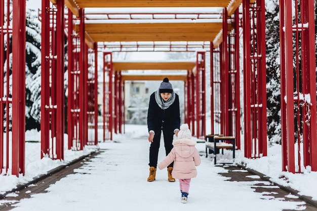 Happy young family walks with baby on winter street, mom, dad, child