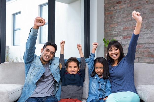 Счастливая молодая семья смотрит телевизор