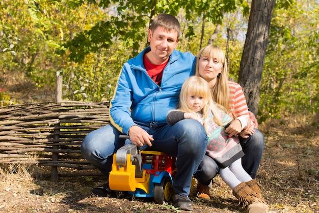 素朴な木製の柵に対して日差しの中で森の屋外でおもちゃのダンプトラックと一緒にポーズをとる母、父と彼らのかわいい金髪の娘と幸せな若い家族