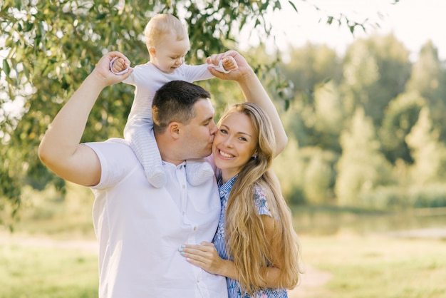 Счастливая молодая семья с маленьким ребенком. папа целует маму в щеку, она счастлива и улыбается.