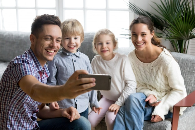 Happy young family with adopted kids smiling taking selfie together