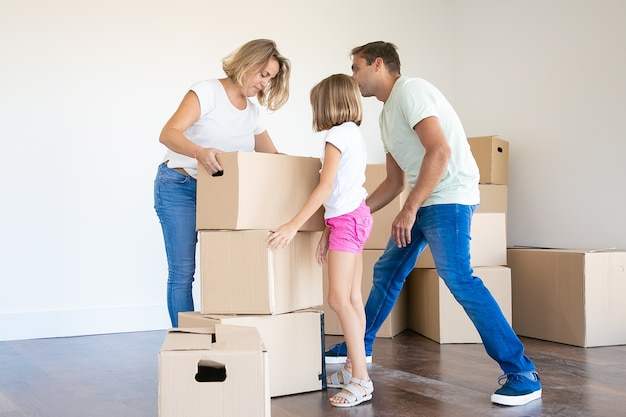 Счастливая молодая семья с картонными коробками, переезжающими в новый дом или квартиру
