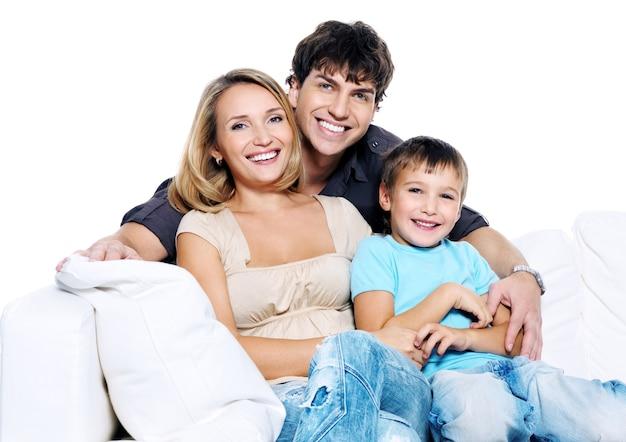 孤立した白いソファに座っている子供と幸せな若い家族