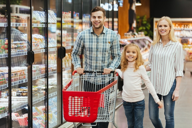 Happy young family with a child walking with a trolley
