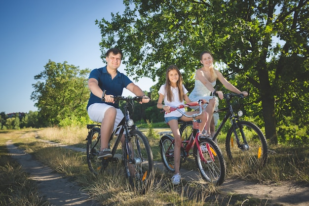 Happy young family with cute daughter cycling at meadow