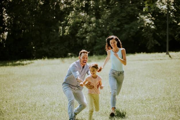晴れた日に公園で走っているかわいい小さな娘と幸せな若い家族