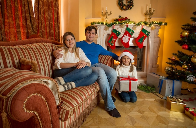 Happy young family with daughter posing at living room with fireplace on christmas eve