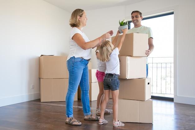 Счастливая молодая семья с движущимися ящиками в новом доме