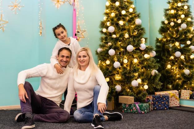 Счастливая молодая семья с одним ребенком держит рождественский подарок и улыбается в камеру