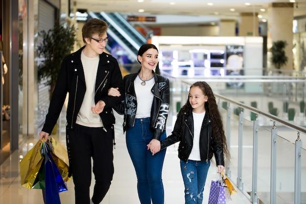 Счастливая молодая семья с бумажными сумками ходя по магазинам на моле. магазинные витрины с одеждой