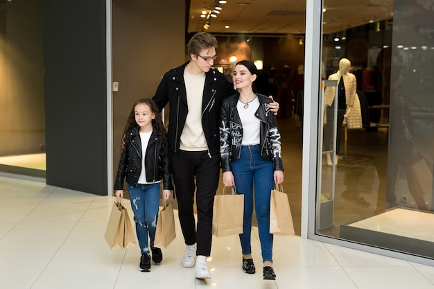Happy young family with paper bags shopping at the mall