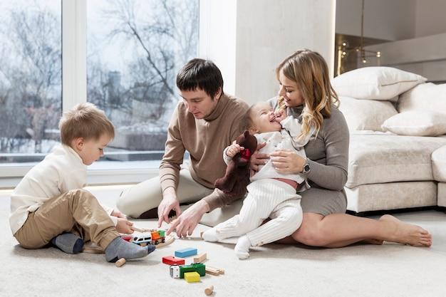 작은 아이들과 함께 행복한 젊은 가족은 거실에서 쉬고 있습니다.