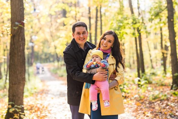 Счастливая молодая семья с дочерью проводить время на открытом воздухе в осеннем парке.
