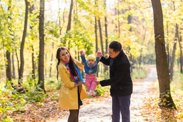 秋の公園で屋外で時間を過ごす娘と幸せな若い家族