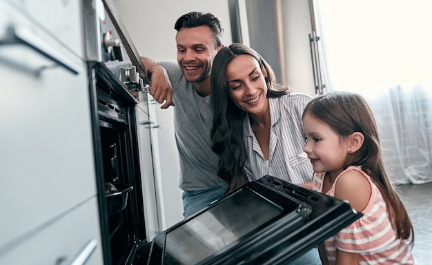 Happy young family with their little cute daughter are peep into the oven while cooking cakes on kitchen.