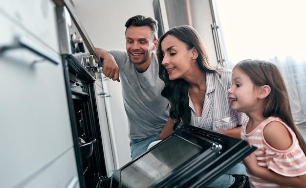 Счастливая молодая семья с маленькой милой дочерью заглядывают в духовку, готовя торты на кухне.
