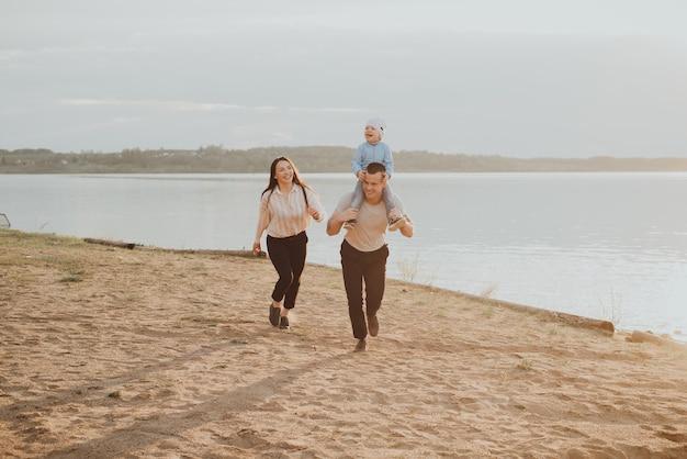 水辺の夏のビーチで遊んで楽しんでいる息子と一緒に幸せな若い家族