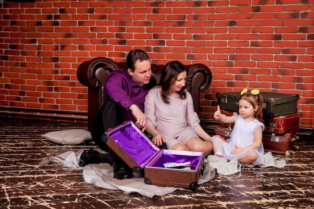 Happy young family with three-year-old girl sitting in attic house with old suitcases and playing cute. lovely pregnant mother, father and daughter in home and play. atmospheric baby's family moments