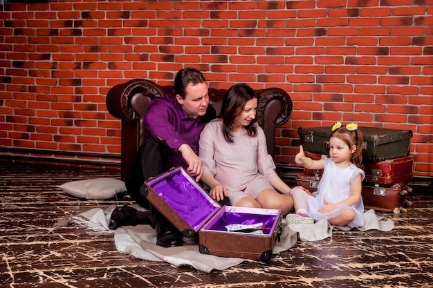 Счастливая молодая семья с трехлетней девочкой сидит на чердаке со старыми чемоданами и играет мило. прекрасная беременная мать, отец и дочь в доме и играют. атмосферные семейные моменты малыша