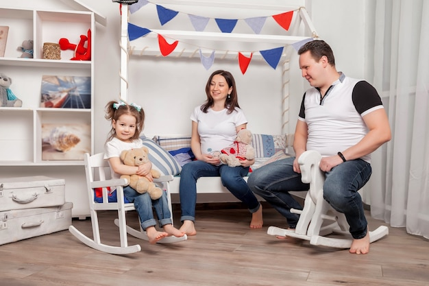 Счастливая молодая семья с трехлетней девочкой сидит в детской комнате и играет мило. прекрасная беременная мать, отец и дочь в доме и разговаривают. атмосферные семейные моменты малыша. копировать пространство