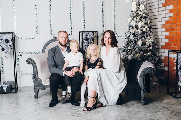 クリスマスツリーで2人の子供と幸せな若い家族