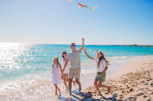 Happy young family with two kids with flying a kite on the beach