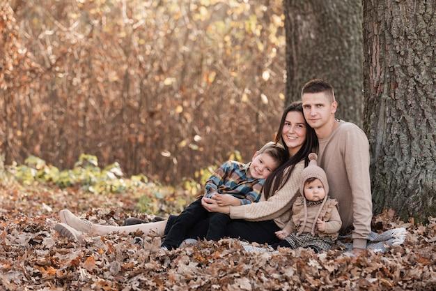 Счастливая молодая семья с двумя маленькими детьми отдыхает и веселится в осеннем парке в солнечный день