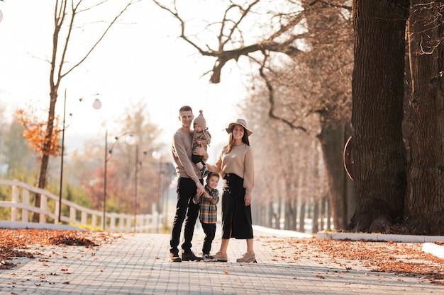 Счастливая молодая семья с двумя маленькими детьми гуляет и развлекается в осеннем парке в солнечный день