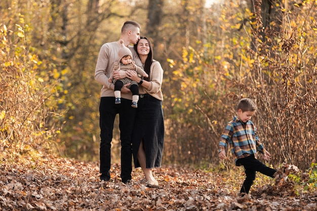 Happy young family with two little children walking and having fun in autumn park on sunny day