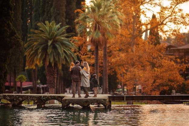 川沿いの森の秋の散歩に2人の息子と幸せな若い家族。