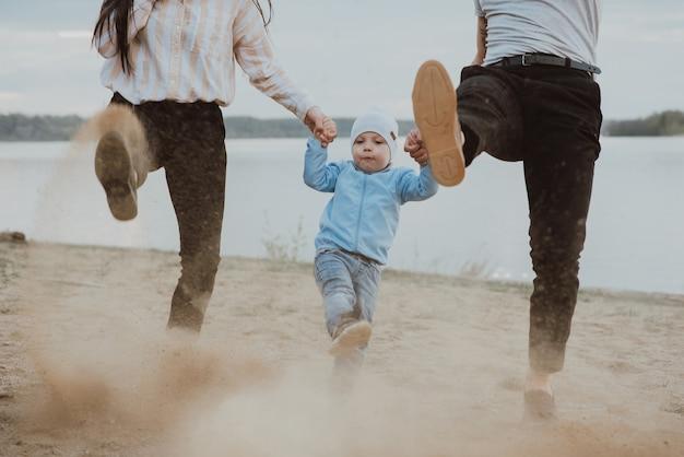 夏のビーチで砂浜で遊ぶ幼い息子と幸せな若い家族