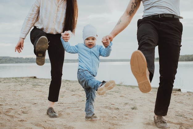 Happy young family with young son playing on the sand on the beach in summer