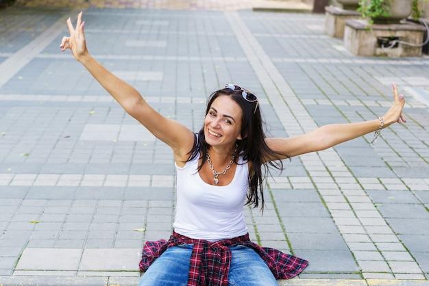 白いtシャツと...通りの歩道のスタイリッシュな女性モデルに座っている幸せな若いファッションの女性。