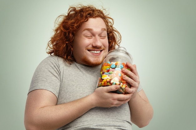 嬉しそうに笑って、目を閉じて幸せな若いデブ肥満男がグッズのガラス瓶で喜び