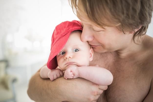 幸せな若い父親と彼の腕の中で小さな新生児を抱いて