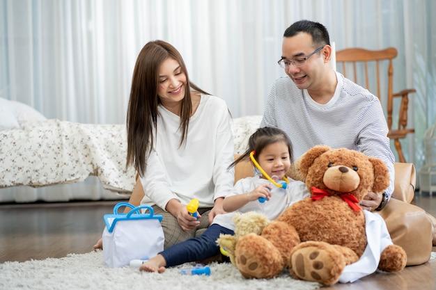Счастливый молодой отец и мать и маленькая дочь, играя с игрушкой, сидя на полу в гостиной, концепция семьи, отцовства и людей