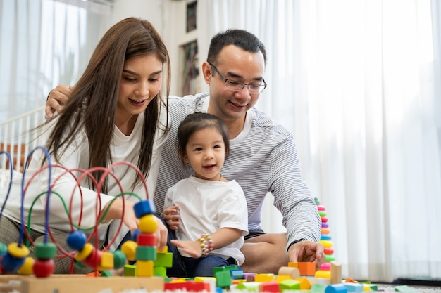 幸せな若い父と母と小さな娘がおもちゃの木製ブロックで遊んで、リビングルーム、家族、親子関係、発達のおもちゃで人々の概念の床に座っています