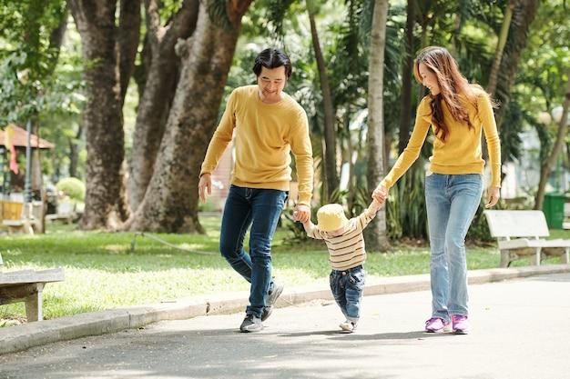 公園で一緒に歩いているときに男の子の手をつないで幸せな若い父と母