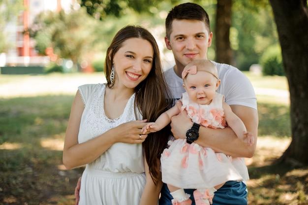 공원에서 귀여운 여자 아기와 함께 산책 행복 한 젊은 아버지와 어머니