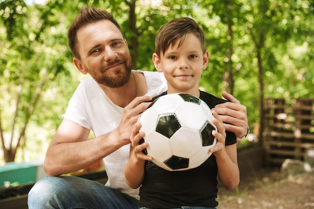 Счастливый молодой отец весело провести время со своим маленьким сыном с футболом