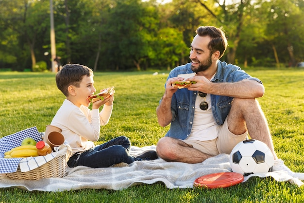 公園で彼の幼い息子と一緒にピクニックをし、サンドイッチを食べて幸せな若い父親