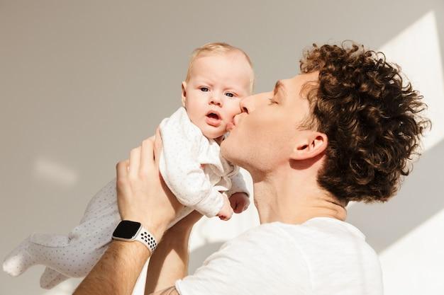 Счастливый молодой отец, держа своего маленького сына, стоя в помещении, целуя