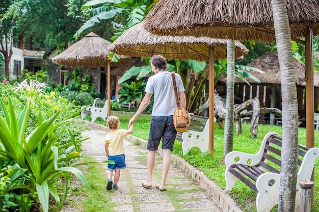 Счастливый молодой отец, держа руку маленького сына и ходить по дороге