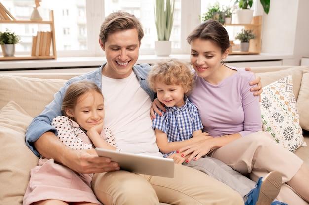 彼の妻と彼の隣に座っている2人のかわいい子供たちながらタブレットを保持している幸せな若い父