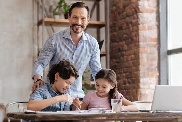 彼らが水彩画で絵を描いている間、彼の小さな子供たちの肩に手を置いて幸せな若い父親