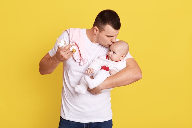 Happy young father looking with tenderness at his baby girl and kissing her on forehead, standing isolated over yellow wall, guy wearing white casual t shirt with his tiny child.