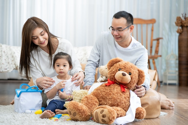 Happy young father and mother and a little daughter playing with toy, sitting on the floor in living room, family, parenthood and people concept