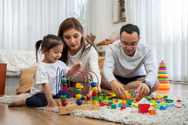 Happy young father and mother and a little daughter playing with toy wooden blocks, sitting on the floor in living room, family, parenthood and people concept with developmental toys